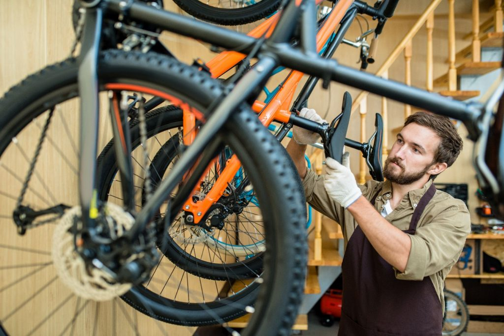 Waist-up portrait of concentrated young mechanic in apron adjusting saddle height while working at modern bicycle repair shop